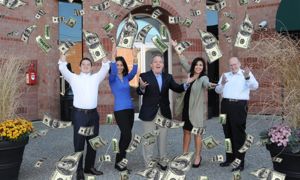 Warren, Melina and three others throwing hundred dollar bills in the air
