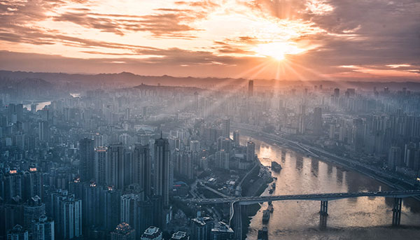 Sun rising over city skyline with river and bridges