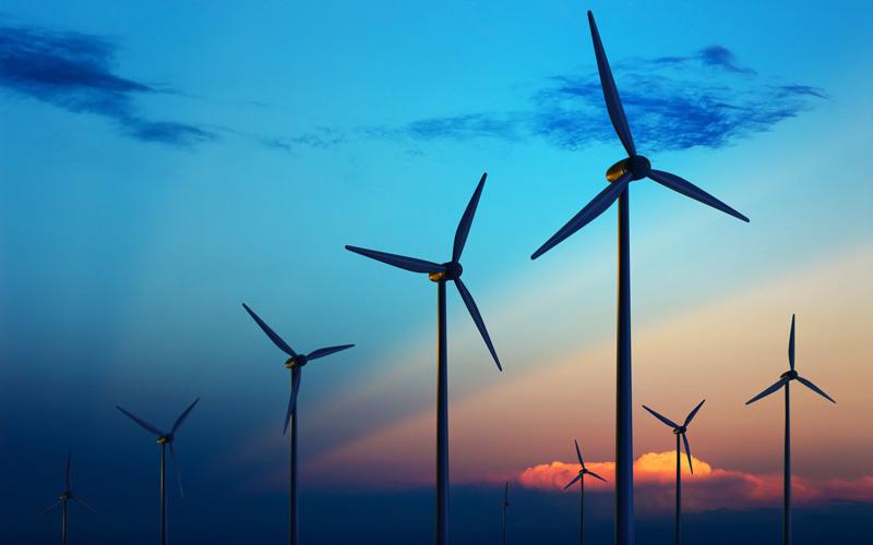 Renewable energy, wind turbines against a deep blue sky at dusk.