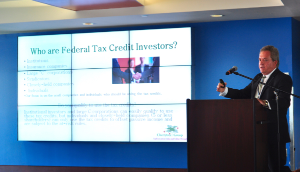 Guest speaker, man presenting at podium, Who are Federal Tax Credit Investors slide on screen