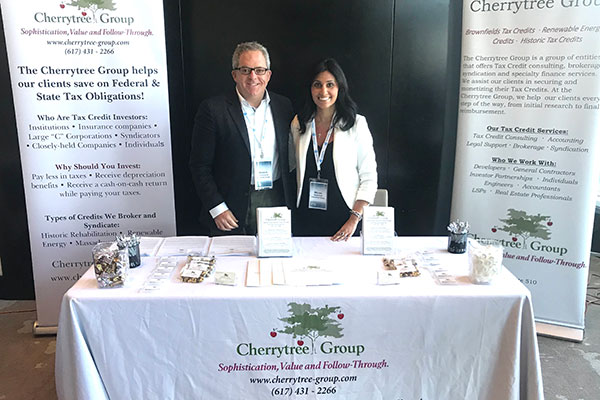 Cherrytree Group trade show booth set up. Warren and Melina standing behind the table skirted with white cloth, displaying business cards and giveaways.