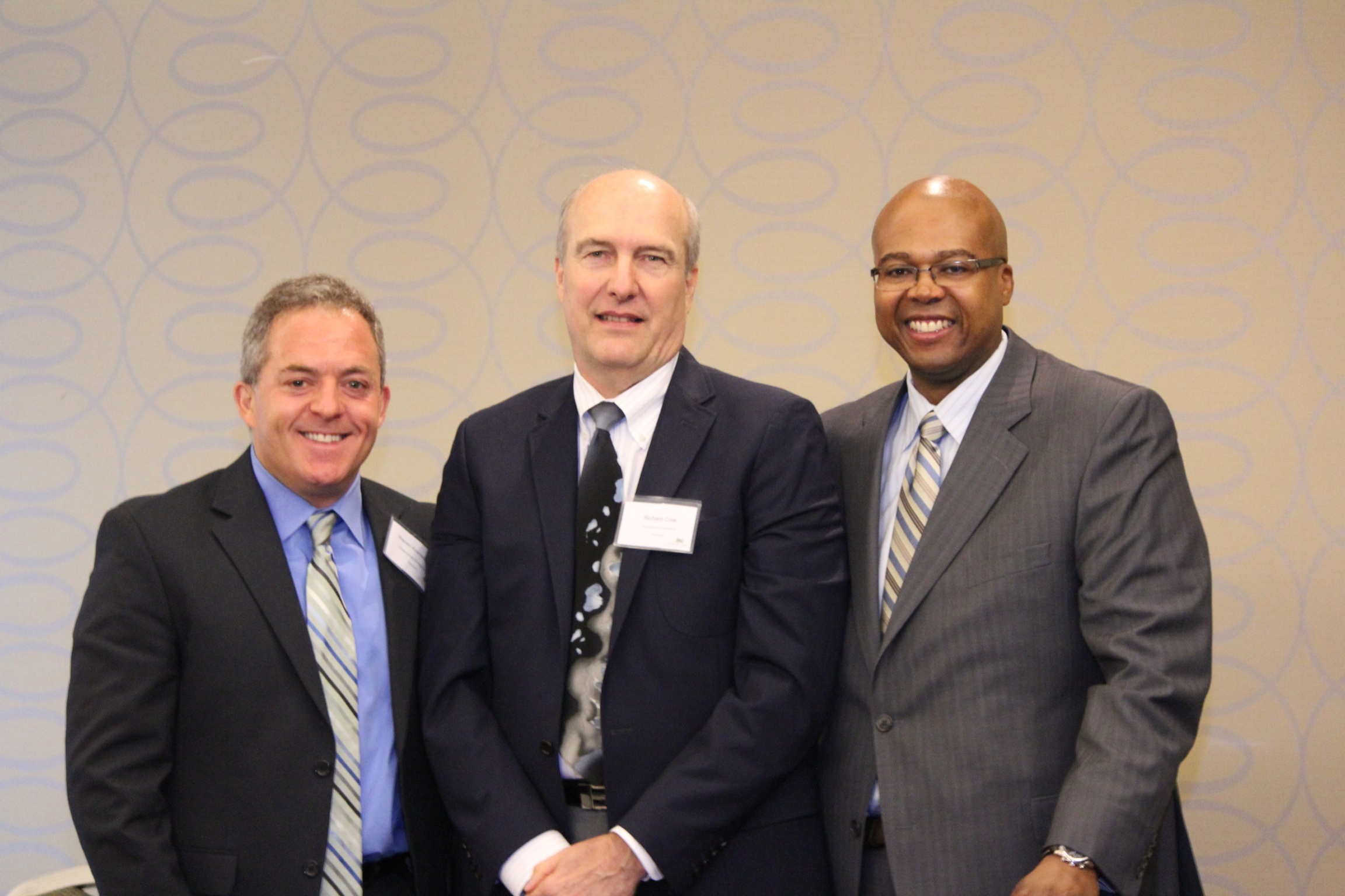 Three men in suits and ties, guest speakers at developing a Brownfields Site event
